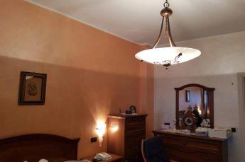 ambientazione illuminazione camera da letto con lampadario e applique